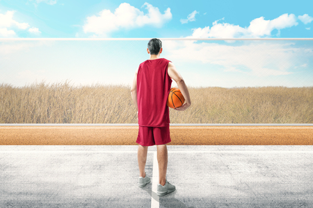 Back view of asian basketball player man standing with ball on his hand in the outdoor basketball court