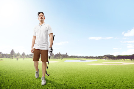 Handsome asian man in white clothes holding iron golf club walking on the golf course with sand bunkers, pond and trees at morning
