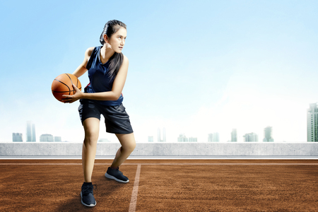 Beautiful asian basketball player woman with ball on her hands on the outdoor basketball court Stock Photo