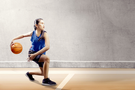 Attraktives asiatisches Mädchen in blauer Sportuniform auf Basketball-Pivot bewegt sich auf dem Basketballplatz mit Holzboden und Betonwandhintergrund