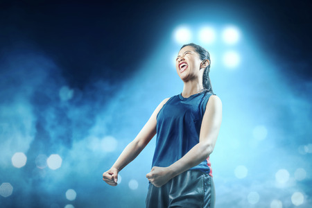 Cheerful asian girl basketball player in blue sportswear with happiness expression in the basketball court with blue spotlights background
