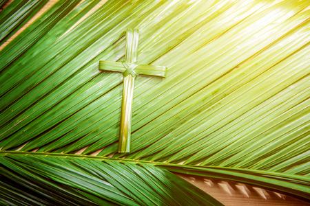 Forma de cruz de hoja de palma en ramas de palma con rayo en fondo de madera. Concepto de Domingo de Ramos Foto de archivo