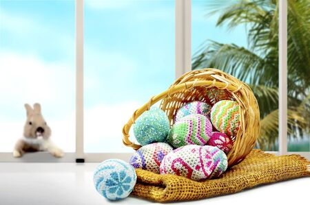 Colorful easter eggs spilled from wooden basket to fabric and table and little bunny on the window glass with palm tree and blue sky background. Happy Easter Stock Photo - 130495361