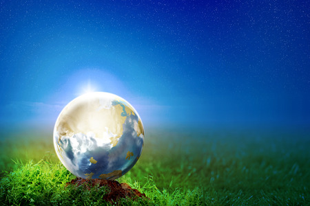 Earth on the soil in meadow at night with star on the sky background. Earth hour concept