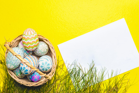 Colorful easter eggs on the wooden basket with grass and blank white paper on yellow background. Happy Easter Stockfoto