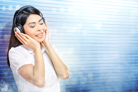 Pretty asian woman in white shirt listening music with headphones over white roller shutter door with smoke and colorful light reflection background
