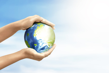Hands holding earth planet over blue sky background. Earth hour concept Standard-Bild - 118503680