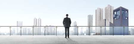Rear view of asian businessman standing on modern terrace and looking at view on the city Stock Photo