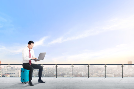 Handsome asian businessman sitting on blue suitcase hold the laptop and working on modern terrace with city view and blue sky background