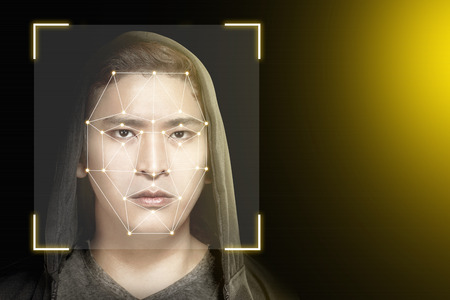 Young asian man in black hoodie using face recognition over dark background. Modern technology concept