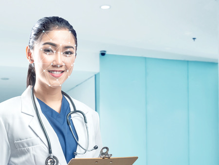 Pretty asian female doctor in white coat and stethoscope holding clipboard using face recognition over hospital background. Modern technology concept Banco de Imagens