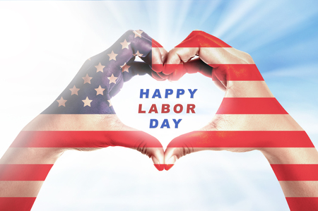 Human hands in heart shape with american flag skin and Happy labor day message over bright background. Labor day concept