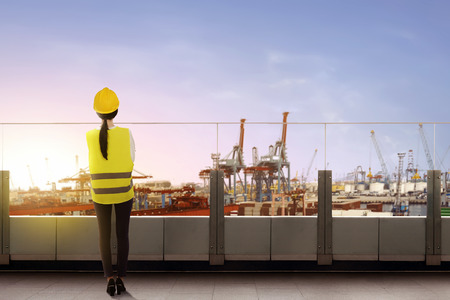 Rear view of asian female worker with safety vest and hard hat standing on office terrace and looking at dock with sunset view background Reklamní fotografie