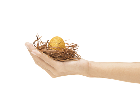 Human hand holding the nest with yellow easter egg isolated over white background. Happy Easter