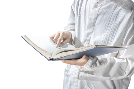 Muslim man standing while reading the quran on his hands isolated over white background Stock Photo