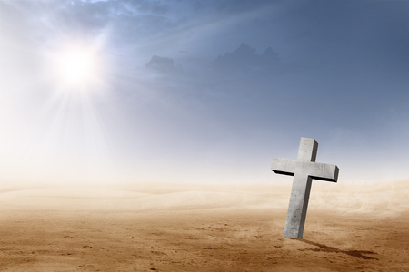 Christian cross on the desert with sun rays over dark sky background