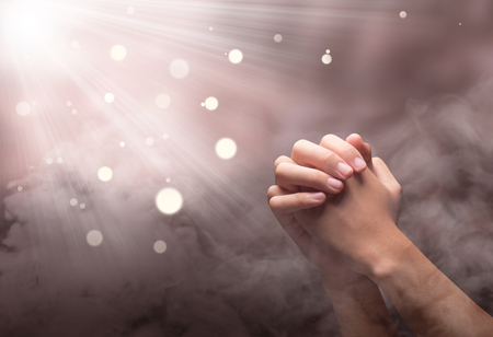 Male hands in praying position with ray over blurry background