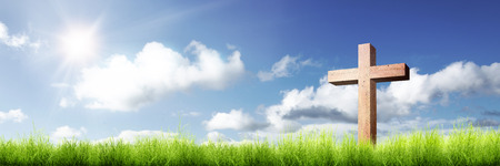 Christian cross on the green grass with sunlight over blue sky background 스톡 콘텐츠