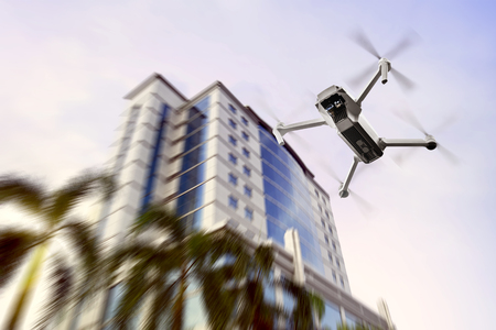 White drone with camera flying to the top of modern building with afternoon background