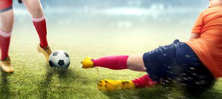 Joueur de football femme en maillot orange s'attaquer à la balle de son adversaire sur le terrain de football Banque d'images