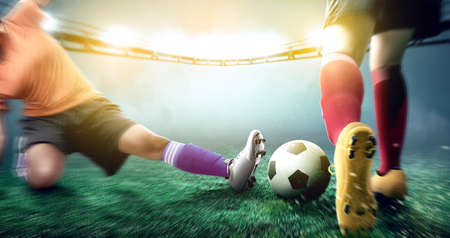 Femme de joueur de football en maillot orange s'attaquer à la balle de son adversaire sur le terrain de football au stade