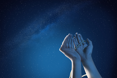 Muslim hands praying with prayer beads at outdoor with night scene background
