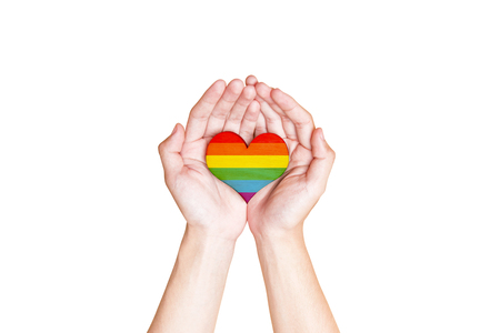 Human hands holding heart with rainbow flag as a symbol of LGBT isolated over white background