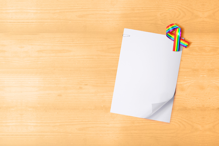 White paper with clip and ribbon with rainbow flag on wooden table. White paper for copyspace. LGBT concept