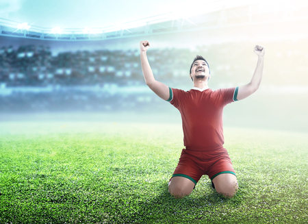 Football player man celebrate his goal with raised arms and kneeling on the football field at stadium