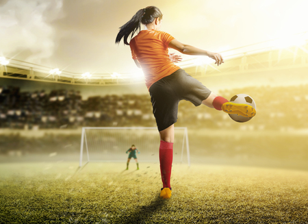 Rear view of asian football player woman in orange jersey kicking the ball in the penalty box on football field at stadium Reklamní fotografie