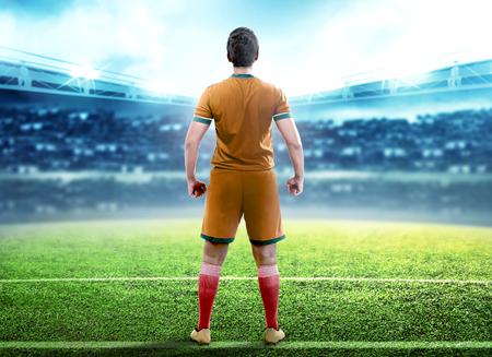 Vista posteriore dell'uomo del giocatore di football in piedi nel mezzo del campo di calcio sullo stadio