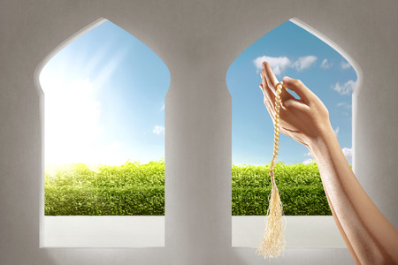Muslim hands praying with prayer beads in the mosque with garden view from window arches over blue sky background Stockfoto