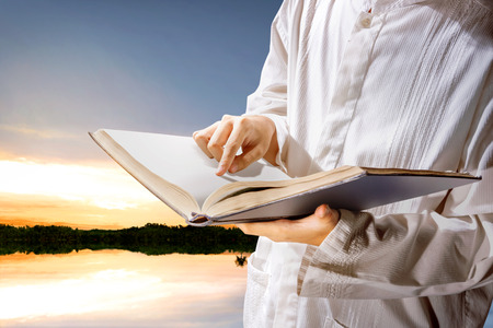 Muslim man standing while reading the quran on his hands at outdoor with lakes and sunset background