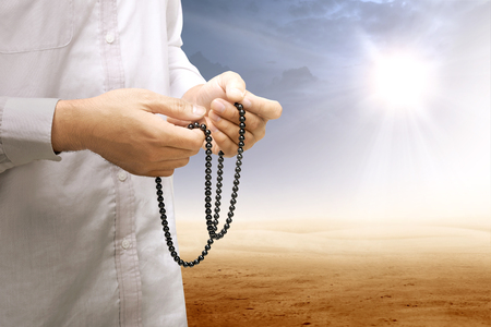 Muslim man praying with prayer beads on his hands on desert with sun rays and dark sky background