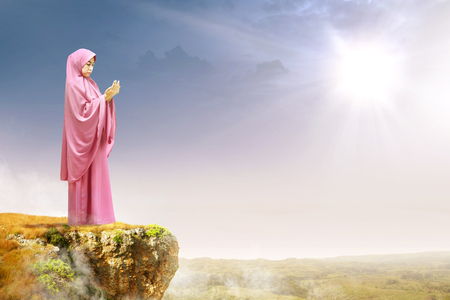 Asian muslim woman in veil raised hands and praying on the edge of the cliff with sunlight and landscapes background