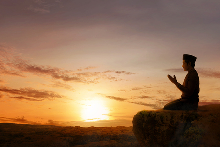 Asian muslim man sitting in pray position while raised hands and praying on the edge of the cliff with sunset and landscapes background