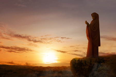 Asian muslim woman in veil raised hands and praying on the edge of the cliff with sunset and landscapes background Stockfoto