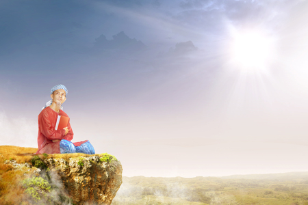 Asian muslim man with turban in his head sitting and holding the quran on the edge of the cliff with sunlight and landscapes background