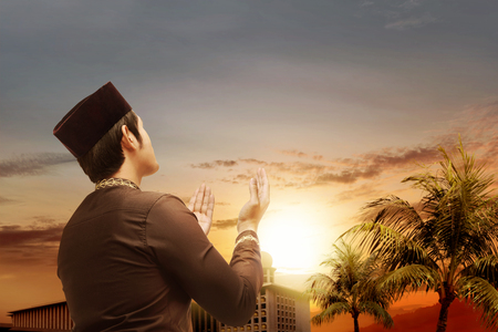 Rear view of asian muslim man standing and praying while raised hands with beautiful mosque with palm trees and sunset on the sky background