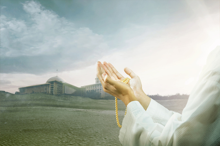 Muslim man praying with prayer beads on his hands on the sand dune with mosque and dark sky background
