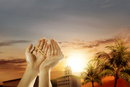 Muslim man praying with prayer beads on his hands and mosque with palm trees over sunset background