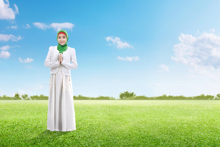 Asian muslim woman in veil praying on the green grass field with blue sky background Stockfoto