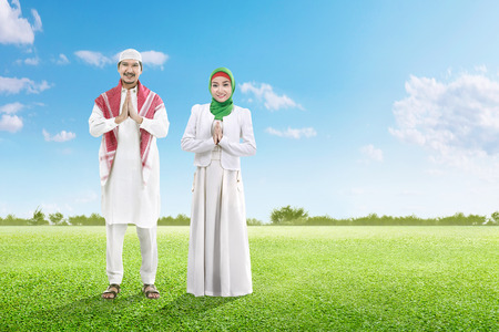 Asian muslim man with cap and muslim woman with veil praying together on the green grass field with blue sky background Stockfoto