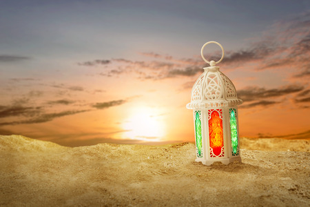 Arabic lamp with beautiful light on the sand dunes with sunset background