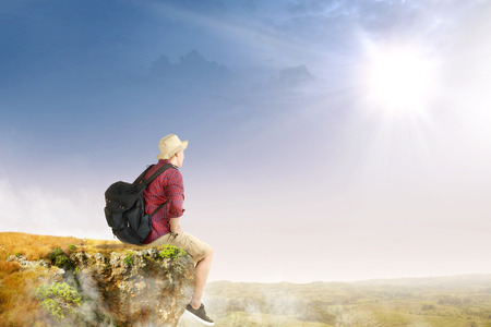 Rear view of asian traveler man with hat and backpack sitting on the edge of cliff looking at landscapes with sunlight background
