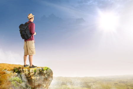 Rear view of asian traveler man with hat and backpack standing on the edge of cliff looking at landscapes with sunlight background