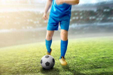 Football player man kicking the ball on football field at stadium
