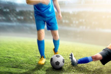 Femme de joueur de football s'attaquer au ballon de son adversaire sur le terrain de football au stade