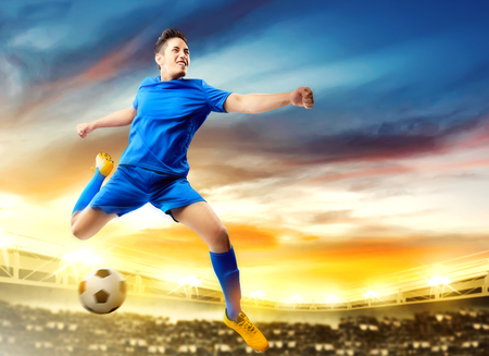Asian football player man jumping and kicking the ball in the air on football field at stadium