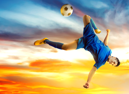 Asian football player man jumping and kicking the ball in the air with sunset background